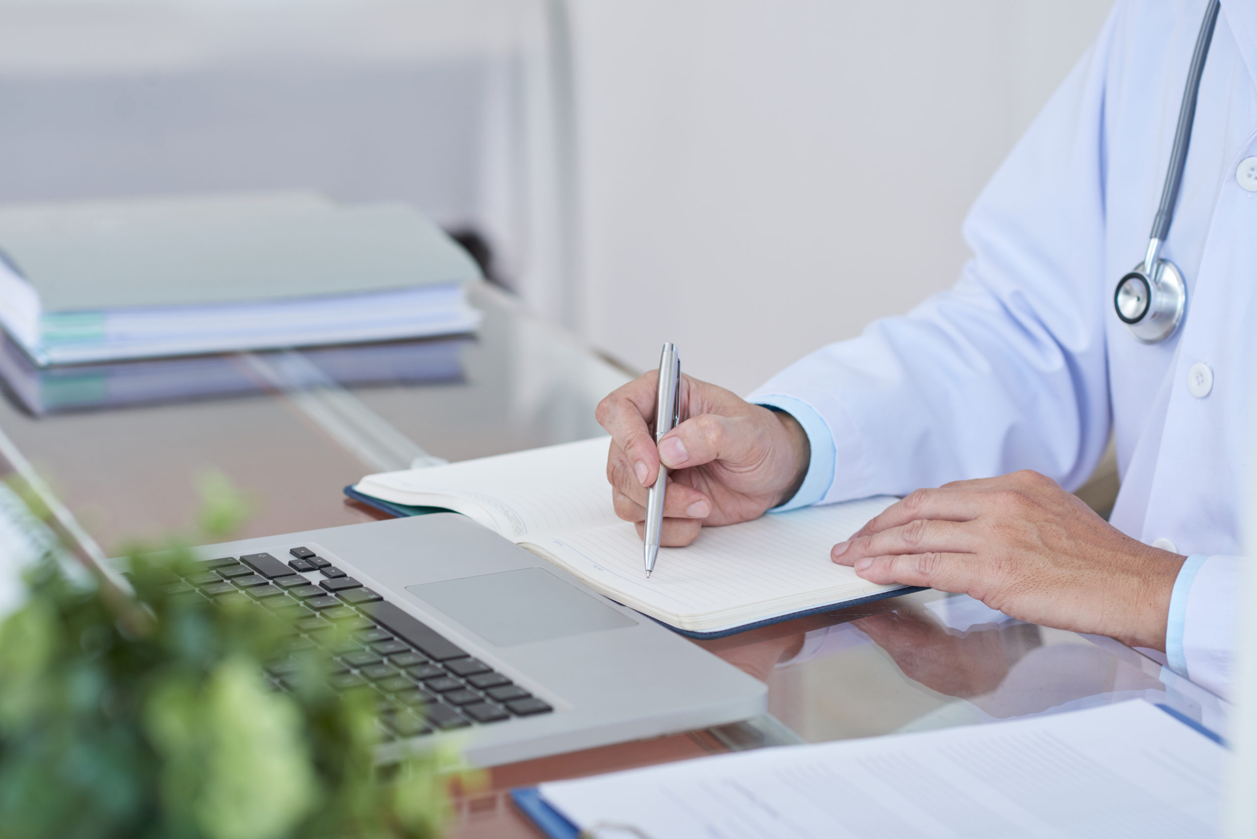 Close-up of male doctor sitting at the table and planning his work day in notepad at office
