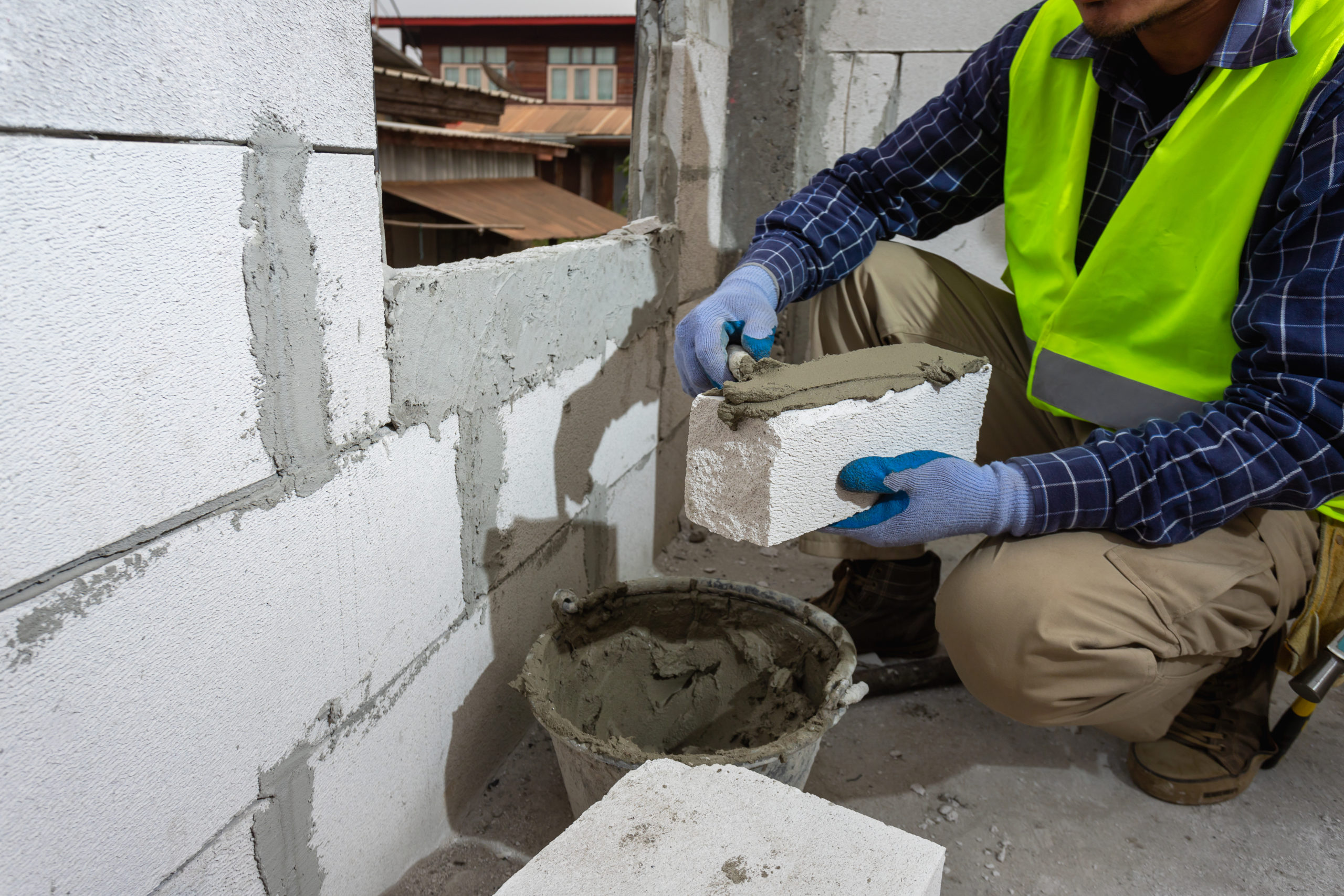bricklayer builder working with autoclaved aerated concrete blocks. Walling, installing bricks on construction site, Engineering and constructions concepts.