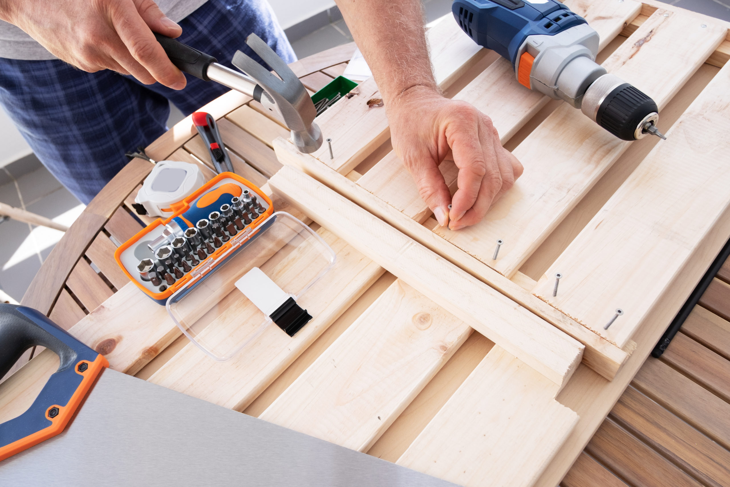 Hands driving nail with hammer into wooden shelf laying on round table. Craftsman working at balcony during self-isolation. House improving, DIY and home decoration during quarantine concept